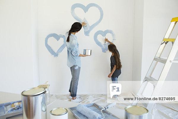 Mutter und Tochter malen blaue Herzen an der Wand im neuen Haus