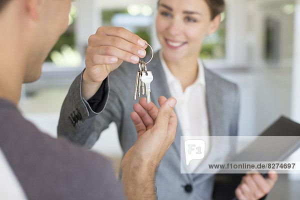Immobilienmakler geben Mann Hausschlüssel
