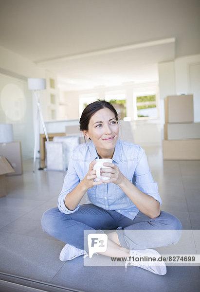 Glückliche Frau genießt Kaffee zwischen Pappkartons