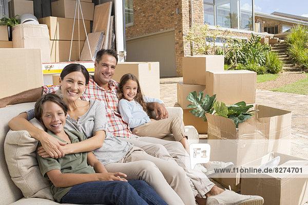 Porträt einer lächelnden Familie  die auf einem Sofa in der Nähe eines fahrenden Lieferwagens in der Einfahrt sitzt.