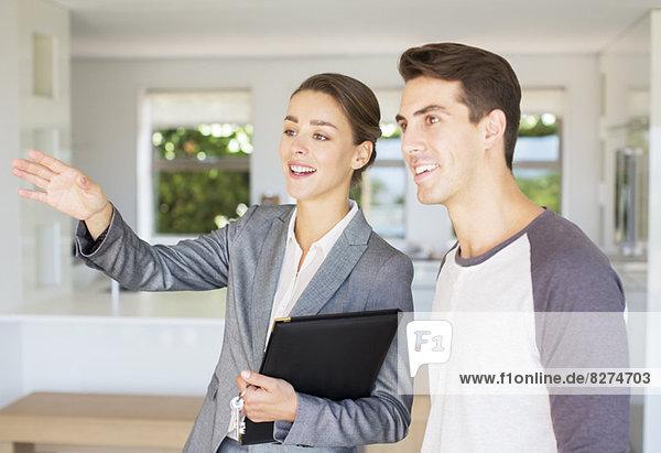 Immobilienmakler zeigt Mann Haus