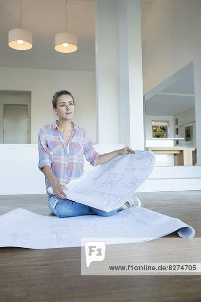 Frau mit Blaupausen auf dem Boden im neuen Haus