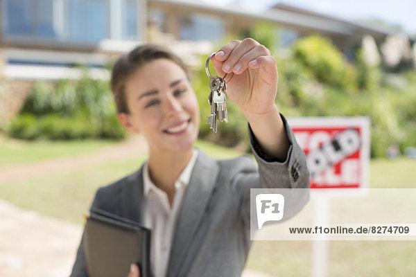 Porträt des Immobilienmaklers mit Hausschlüssel vor dem Haus