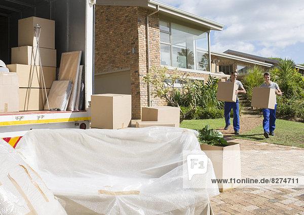 Umzugsunternehmen  die Kartons vom Haus zum Umzugswagen transportieren