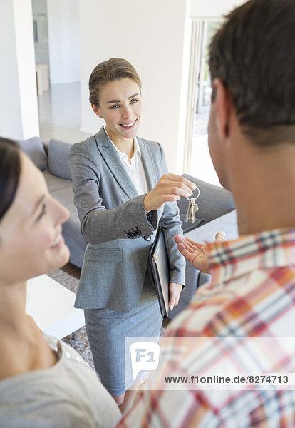 Immobilienmakler geben Paar Hausschlüssel