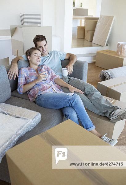 Paar Entspannung mit Kaffee auf dem Sofa im neuen Haus