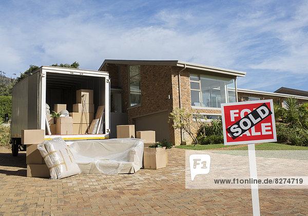 Verkauftes Schild und Umzugswagen außerhalb des Hauses