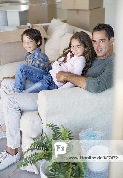 Vater und Kinder entspannen sich auf dem Sofa zwischen Pappkartons