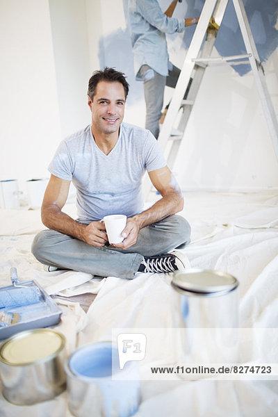 Porträt eines lächelnden Mannes beim Kaffeetrinken unter den Malutensilien