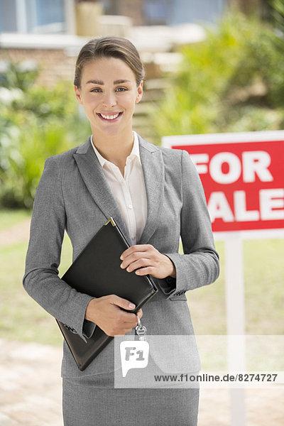 Porträt eines lächelnden Immobilienmaklers bei For Sale Schild