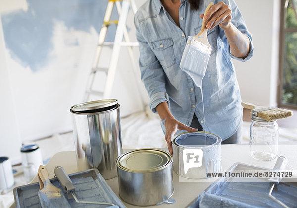 Frau hält Pinsel mit blauer Farbe in der Hand
