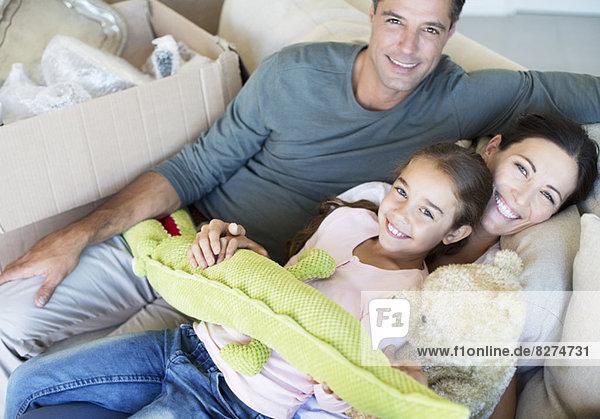 Porträt einer lächelnden Familie mit Plüschtieren auf dem Sofa