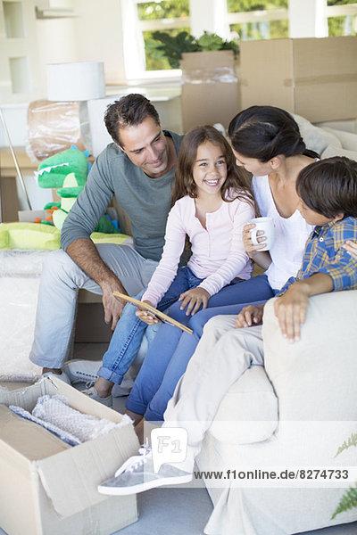 Familie entspannt auf dem Sofa im neuen Haus