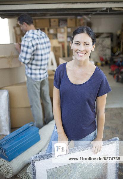 Frau hält Bild in der Einfahrt zwischen Pappkartons