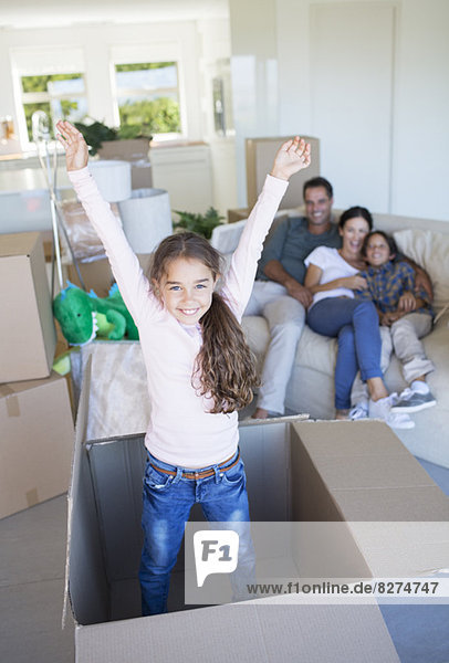 Mädchen beim Spielen im Karton im neuen Haus