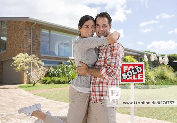Porträt eines lächelnden Paares  das sich vor dem neuen Haus umarmt.