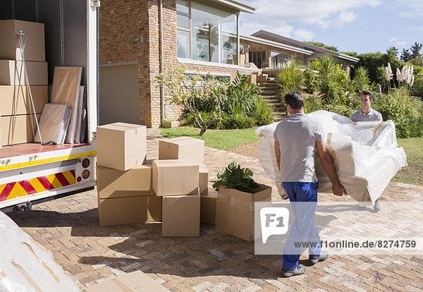 Umzugsunternehmen mit Sofa vom Umzugswagen zum Haus