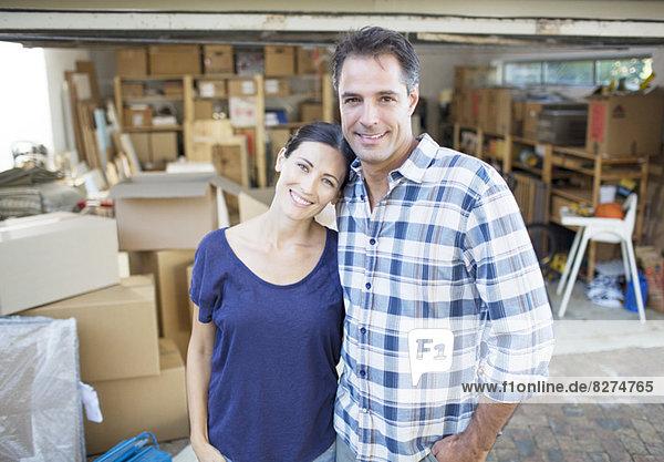 Porträt eines lächelnden Paares außerhalb der Garage zwischen Pappkartons