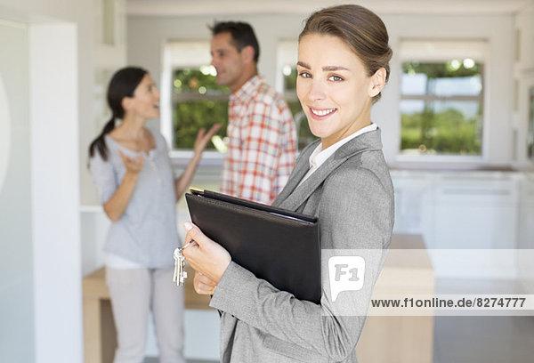 Porträt eines lächelnden Immobilienmaklers mit Paar im Hintergrund