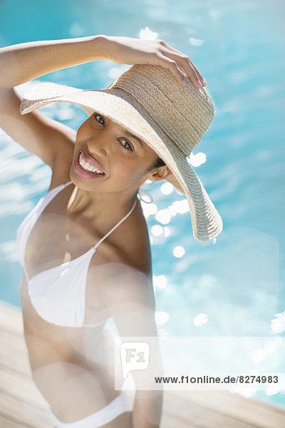 Porträt einer lächelnden Frau am Pool