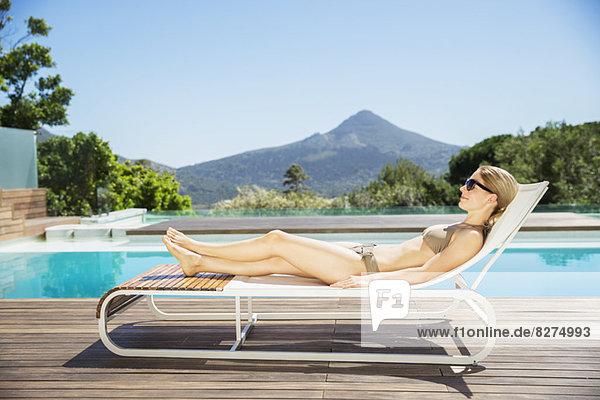 Frau entspannt sich auf dem Sessel am Pool