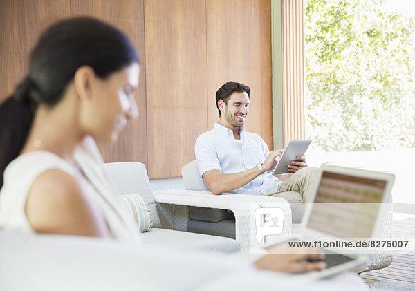 Paar mit digitalem Tablett und Laptop im Wohnzimmer