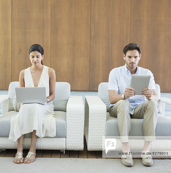Paar mit digitalem Tablett und Laptop in Sesseln