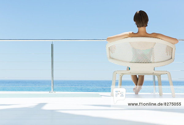 Frau im Stuhl mit Blick auf den Ozean