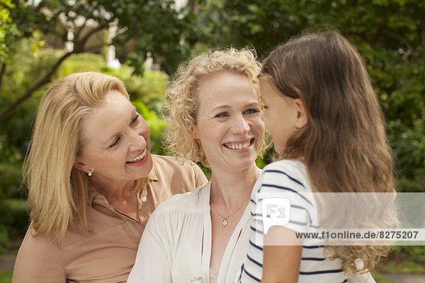 Drei Generationen von Frauen lächeln im Freien