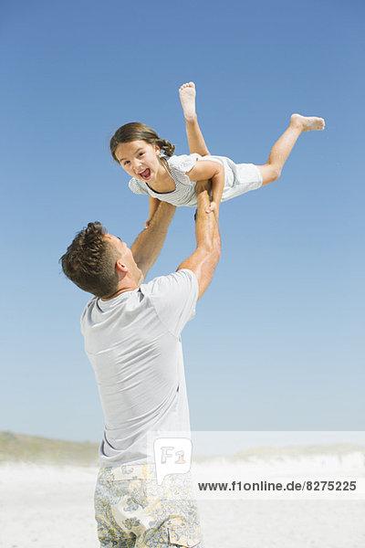 Vater hebt Tochter am Strand hoch