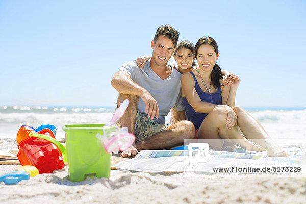 Porträt einer lächelnden Familie am Strand sitzend