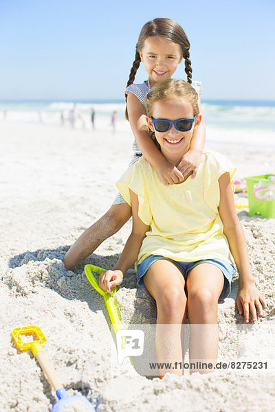 Mädchen spielen im Sand am Strand