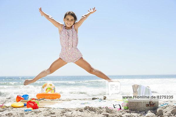 Mädchen springen am Strand