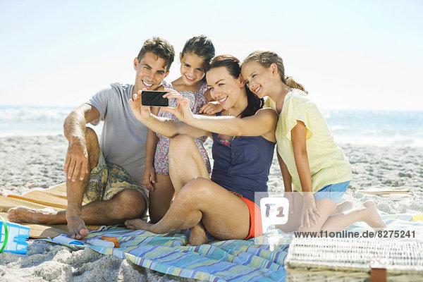 Familie beim Selbstporträt am Strand