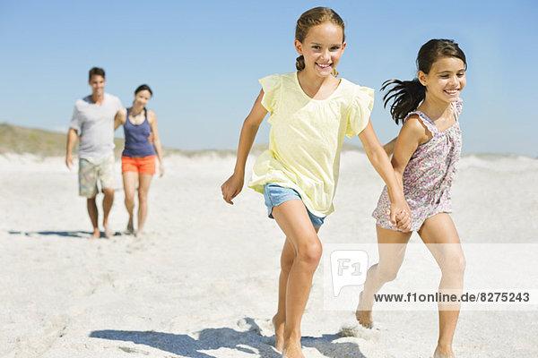 Mädchen beim Händchenhalten und Laufen am Strand