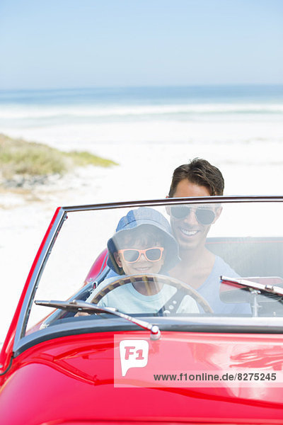 Father and son driving convertible on beach