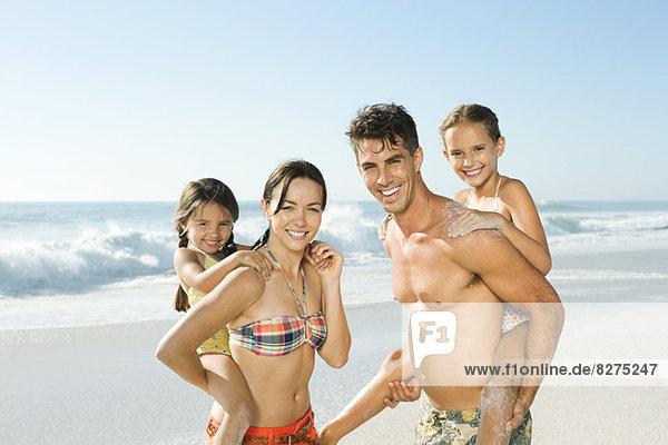 Eltern mit Töchtern huckepack am Strand