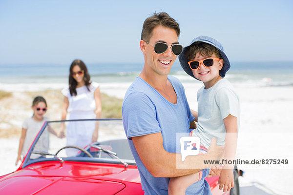 Vater und Sohn lächeln in der Nähe des Cabrios am Strand