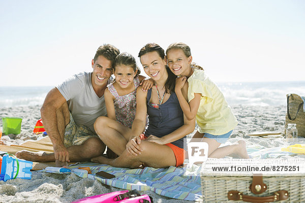 Porträt der lächelnden Familie auf Decke am Strand