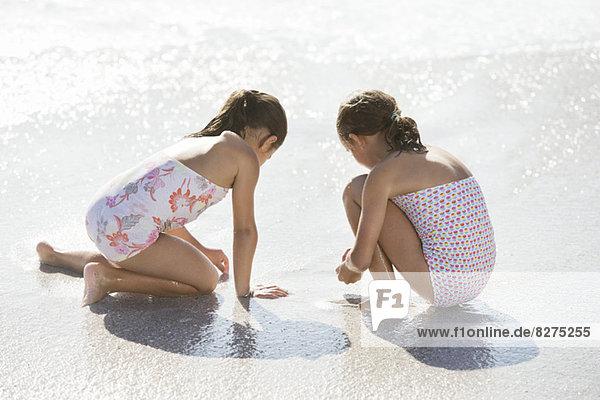 Mädchen beim gemeinsamen Surfen am Strand