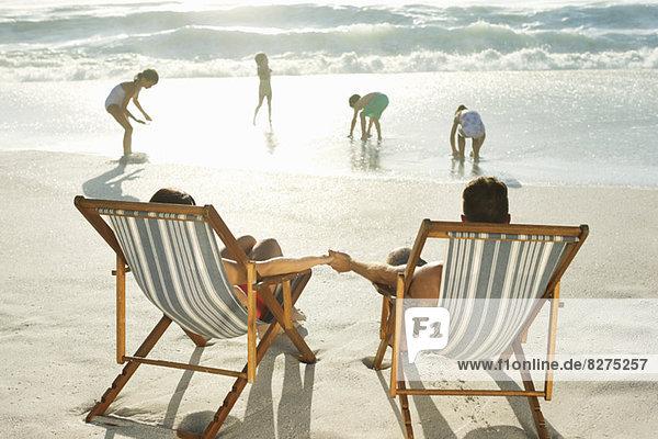 Eltern beobachten Kinder beim Spielen am Strand
