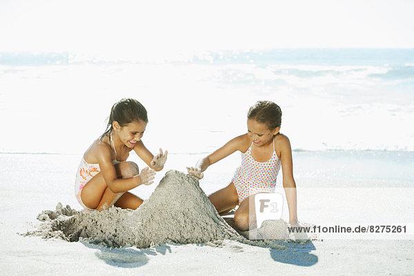 Mädchen bauen Sandburg am Strand