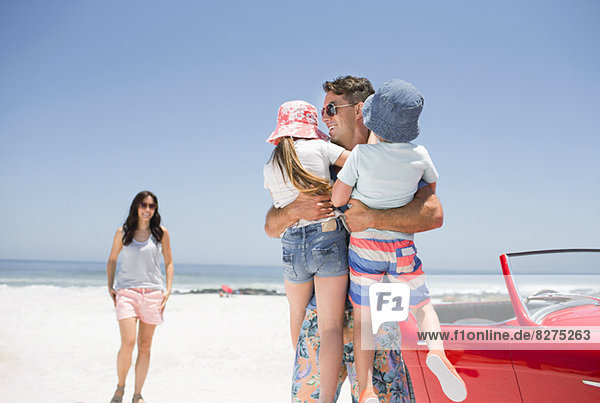 Vater hält Kinder am Strand in der Nähe von Cabriolet