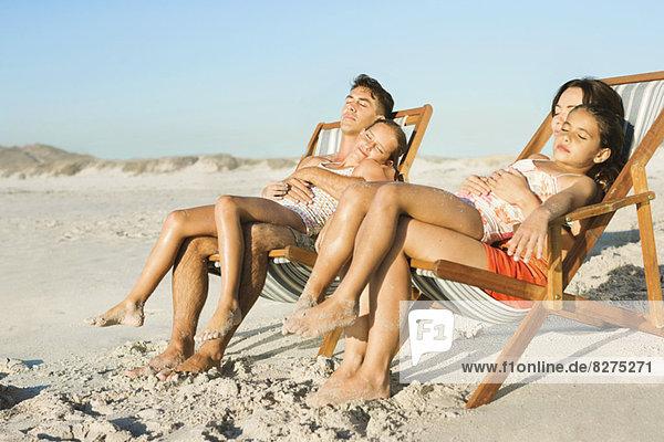 Familie schläft in Liegestühlen am Strand