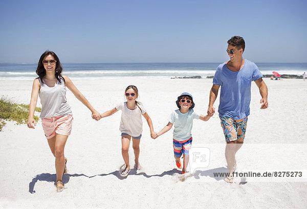 Familie hält sich an den Händen und geht am Strand spazieren