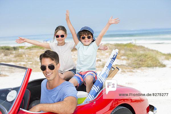 Vater und Kinder lächeln im Cabrio am Strand