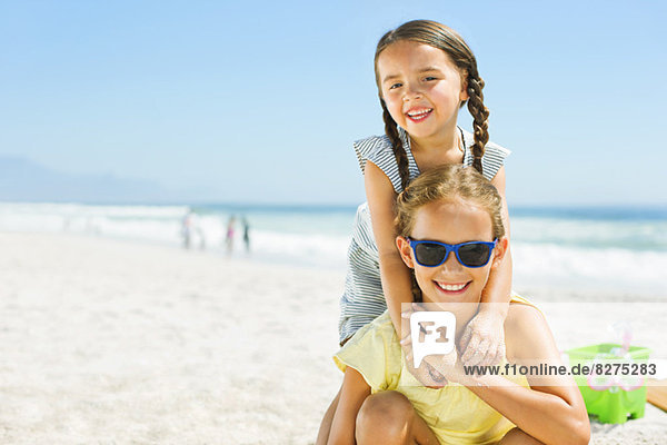 Portrait of smiling girls hugging on beach