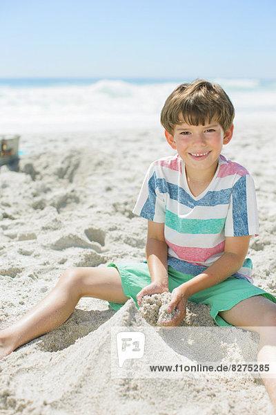 Junge baut Sandburg am Strand
