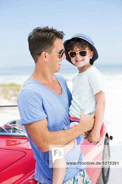 Vater und Sohn lächeln am Strand neben dem Cabriolet