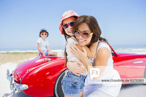 Mutter und Tochter beim Umarmen mit dem Cabrio am Strand